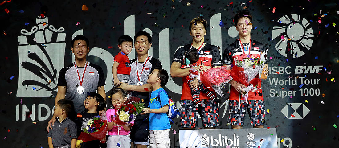 Kevin Sanjaya Sukamuljo/Marcus Fernaldi Gideon (right) and Hendra Setiawan/Mohammad Ahsan at the championship podium stage along with their children.